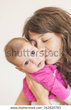 Family Concept: Portrait of Young Mother Taking Care of Her Little Newborn Infant Baby Indoors. Vertical Image Composition - stock photo