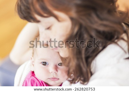 Family Concepts: Portrait of Caring Caucasian Mother and Her Infant Daughter Sitting Together Embraced.Horizontal Image Composition - stock photo