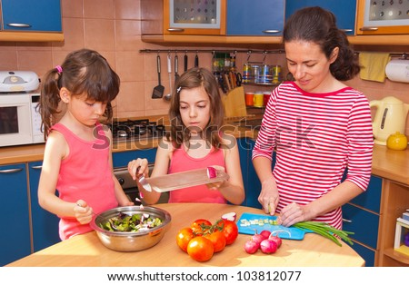 Family cooking at home. Happy smiling mother with kids cook healthy food together at kitchen. Family preparing salad - stock photo