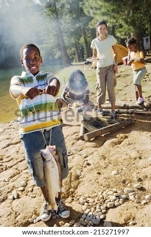Family cooking food on camping trip beside lake, boy (8-10) holding aloft fish in foreground, smiling, portrait - stock photo