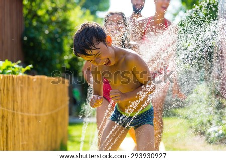 Family cooling down with sprinkler in garden, lots of water splashing around - stock photo