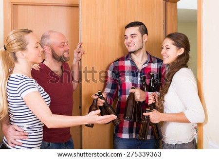 Family couple welcoming russian visitors with beer bottles at home - stock photo
