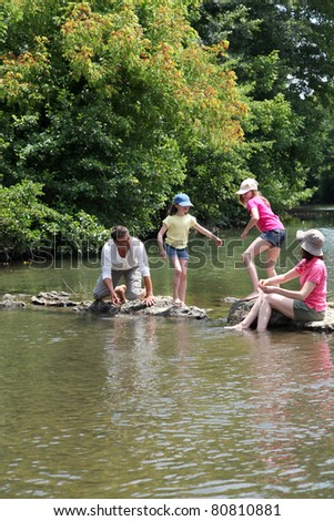 Family crossing river in summer - stock photo