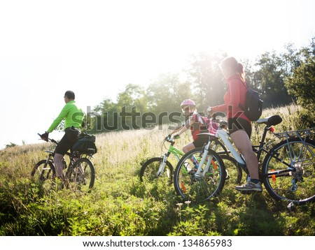 family cycling in summer - stock photo