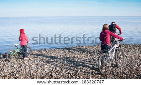 family cycling next to sea - stock photo