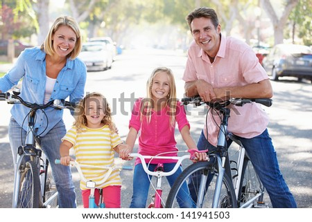 Family Cycling On Suburban Street - stock photo