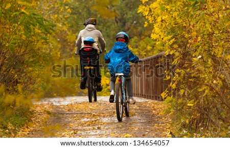Family cycling outdoors, father and kids on bikes, golden autumn in park - stock photo