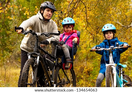 Family cycling outdoors, golden autumn in park, farher and kids on bikes, family sport - stock photo