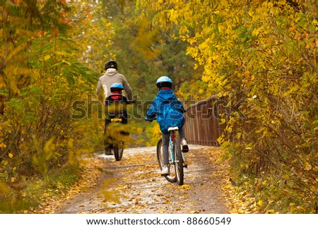 Family cycling outdoors, golden autumn in park. Father with kids on bicycles - stock photo
