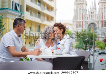 Family day.  Adult daughter drinking tea with her senior parents while sitting in sidewalk cafe. - stock photo