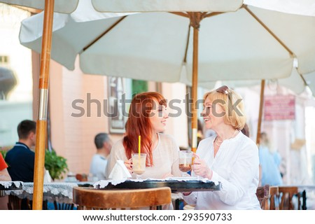 Family day. Aged mother and her adult daughter drinking coffee at sidewalk cafe. - stock photo