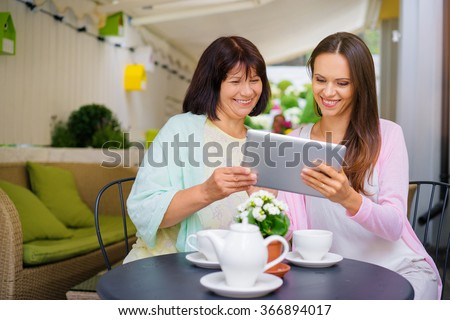 Family day. Aged woman and her adult daughter using tablet computer at cafe. - stock photo