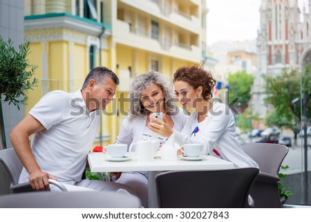 Family day. Elderly loving couple and their adult daughter using smartphone together while sitting in sidewalk cafe. - stock photo
