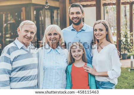 Family day. Happy family of five people bonding to each other and smiling while standing at the back yard of their house together - stock photo