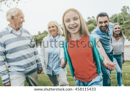 Family day. Happy little girl enjoying time with her family while walking outdoors together - stock photo