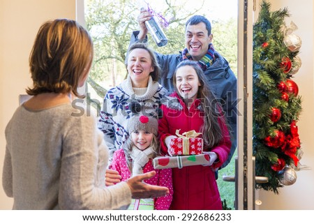 Family delivering Presents at Christmas time. They all look happy and ready to celebrate. - stock photo