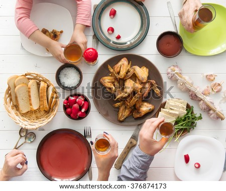 family dinner with roasted chicken wings - stock photo