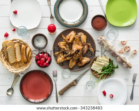 family dinner with roasted chicken wings top view - stock photo