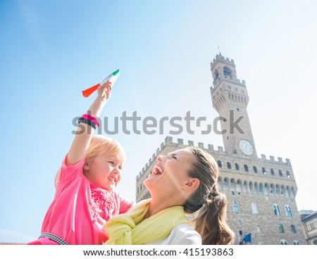 Family discovering old Italian treasures in Florence. Happy mother and daughter with Italian flag near Palazzo Vecchio - stock photo
