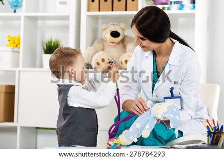 Family doctor examination. Little child visiting pediatrician playing with stethoscope. Beautiful female medical freckled doctor  communicating with cute young patient. Paediatrics medical concept - stock photo