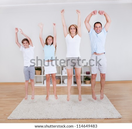 Family Doing Stretching Exercises On The Carpet At Home - stock photo