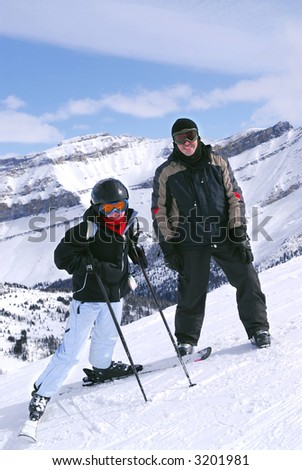 Family downhill skiing vacation - father and daughter in scenic winter Rocky mountains - stock photo