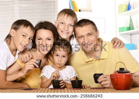 Family drinking tea at table in kitchen - stock photo