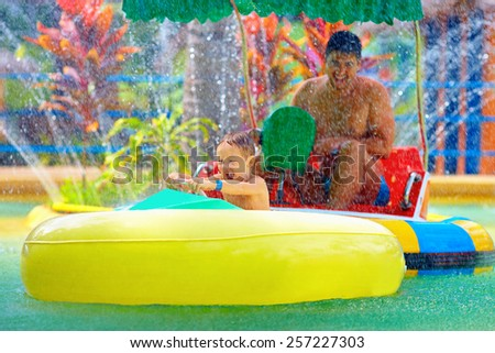 family drive watercraft in aqua park, trying to hit each other - stock photo