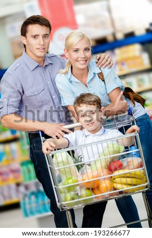 Family drives cart with food and son sitting there. Concept of fresh and healthy food and consumerism - stock photo