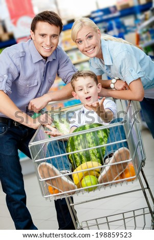 Family drives cart with food and son sitting there with watermelon. Concept of fresh and healthy food and consumerism - stock photo