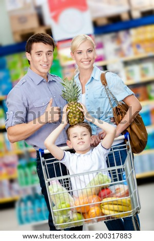 Family drives shopping trolley with food and son sitting there with pine apple on head. Concept of fresh and healthy food and consumerism - stock photo