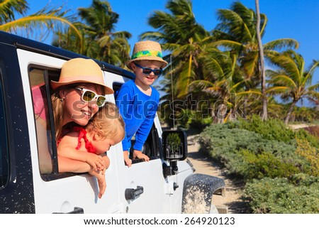 family driving off-road car on tropical beach, vacation concept - stock photo