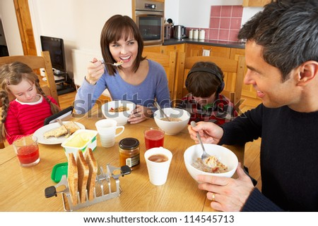 Family Eating Breakfast Together In Kitchen Whilst Children Play With Gadgets - stock photo
