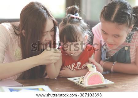 Family eating cake in restaurant instagram style - stock photo