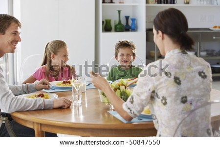 Family eating dinner at round table, in kitchen - stock photo