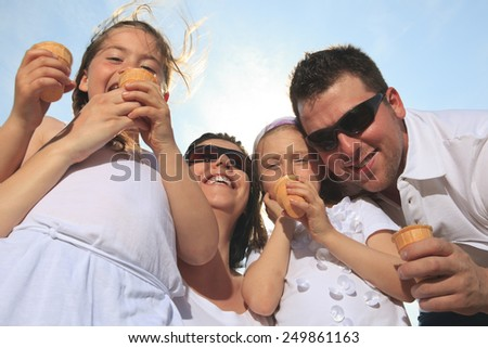 family eating ici-cream in front of ocean - stock photo