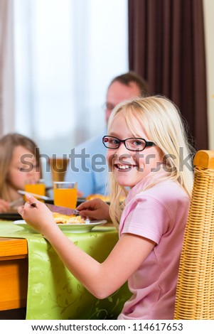 Family eating lunch or dinner and sitting at the table - stock photo