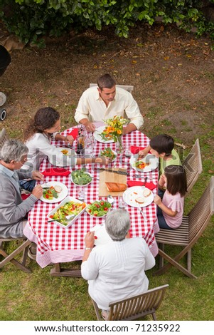 Family eating outside in the garden - stock photo