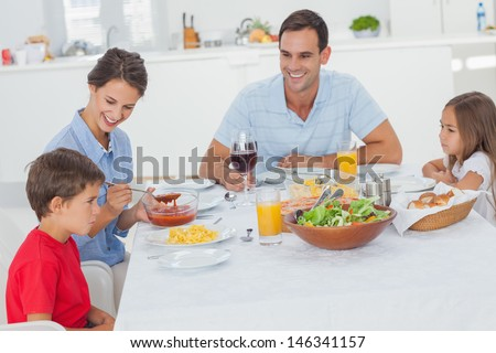 Family eating pasta and salad in the dining room - stock photo