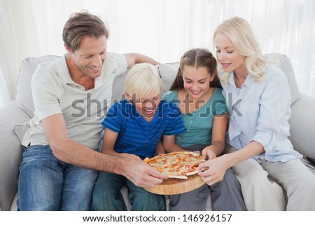 Family eating pizza together sitting on a couch - stock photo