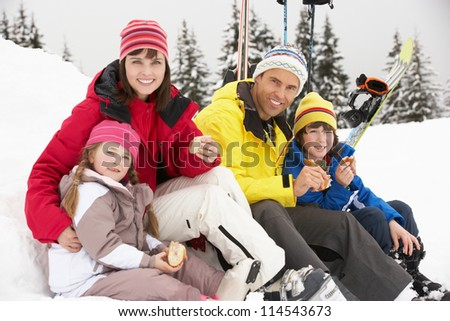 Family Eating Sandwich On Ski Holiday In Mountains - stock photo