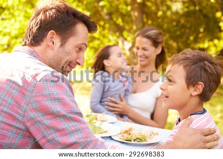 Family eating together outdoors - stock photo