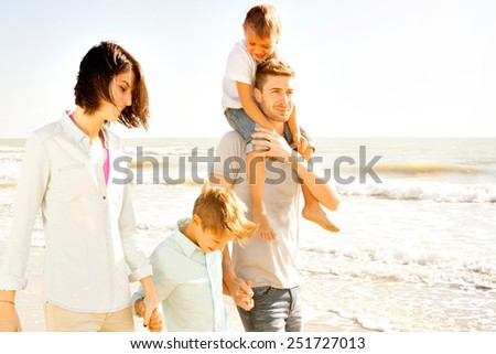 family enjoyed walking on the beach at the sea - stock photo