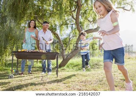 Family Enjoying Barbeque By Lake - stock photo