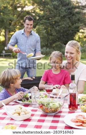 Family Enjoying Barbeque In Garden Together - stock photo