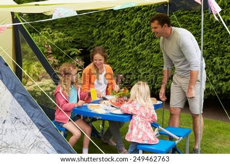 Family Enjoying Meal Outside Tent On Camping Holiday  - stock photo