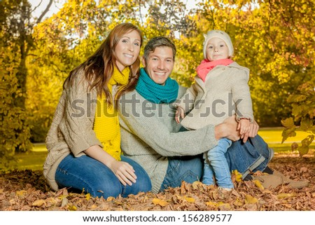 family enjoying season with girl in woods - stock photo