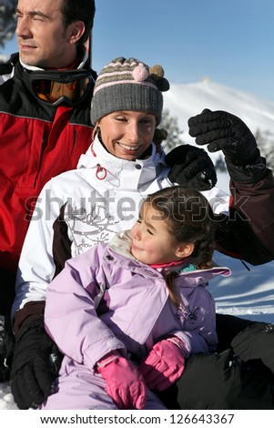 Family enjoying skiing trip - stock photo