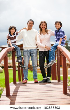 Family enjoying their time together outdoors and smiling - stock photo