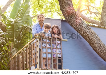 Family enjoying their vacation on a tree house. Son and daughter standing on the balcony of a tree house with their father. Cheerful family relaxing at tree house.  - stock photo